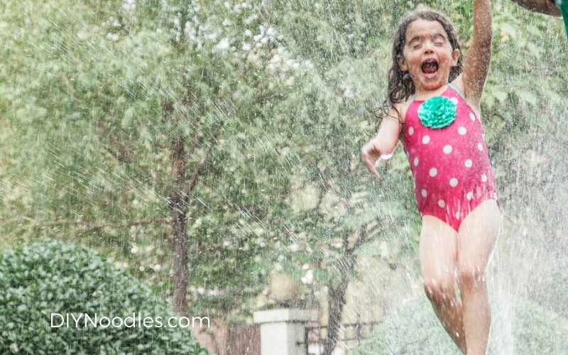 Girl running through the sprinkler in her yard.