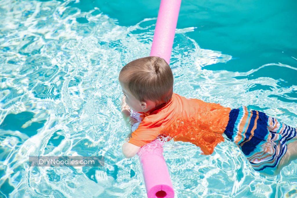 Boy on pool noodle