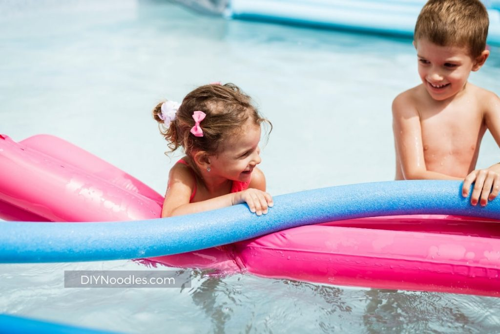 children on raft with pool noodle